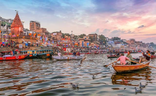 Dashaswamedh Ganges river ghat at twilight with tourists enjoying boating rides in Varanasi, Uttar Pradesh