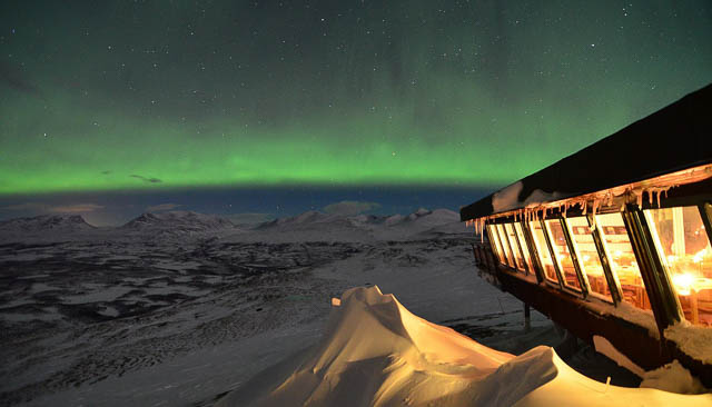 northern lights in front of aurora sky station in abisko, sweden