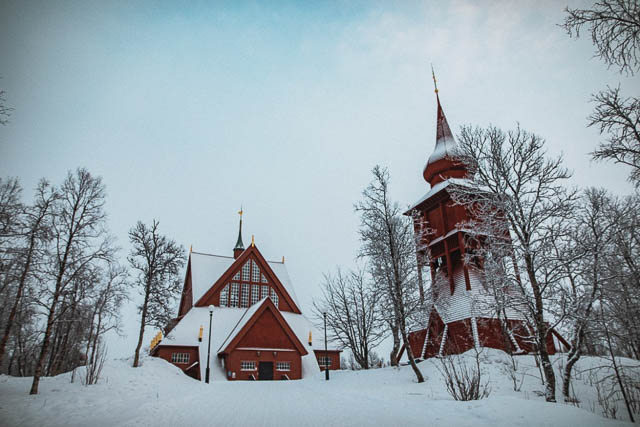 dry trees in front of snow covered jukkasjärvi church, sweden