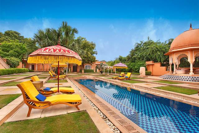 chairs next to pool at the oberoi raj vilas hotel in jaipur, rajasthan