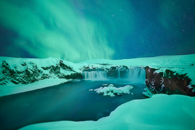 northern lights above godafoss falls iceland
