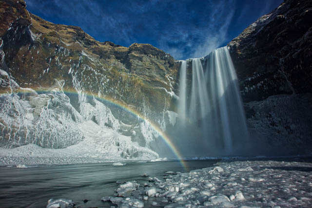 rainbow forming in front of skogafoss waterfalls iceland