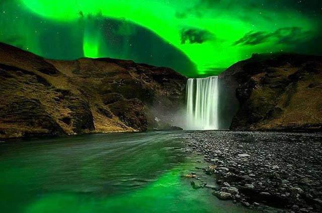polar lights flashing above skogafoss waterfalls iceland