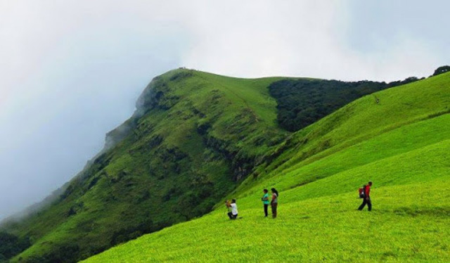 people on one of Chikmagalur green hills Karnataka India