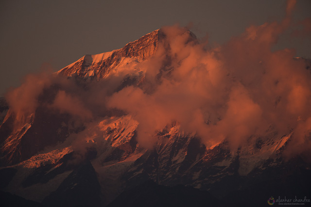 golden shadow falls on one of himalayas peak surrounded by clouds chopta uttarakhand india