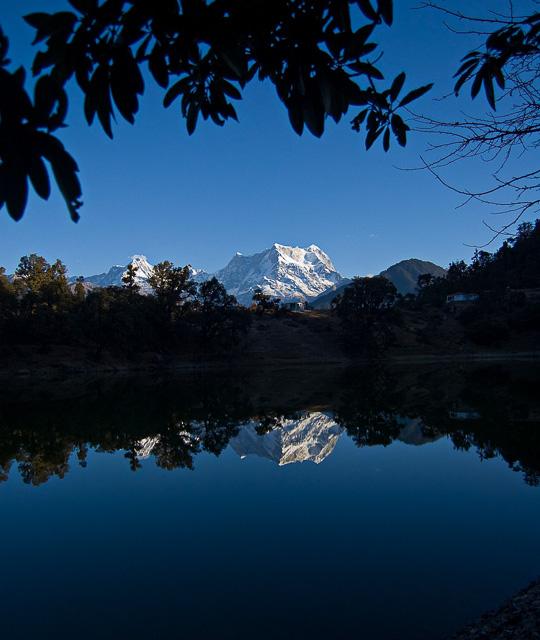 blue sky snow capped mountain reflection on a lake chopta uttarakhand india